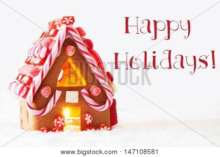Gingerbread House In Snowy Scenery As Christmas Decoration With White Background. Candlelight For Romantic Atmosphere. English Text Happy Holidays