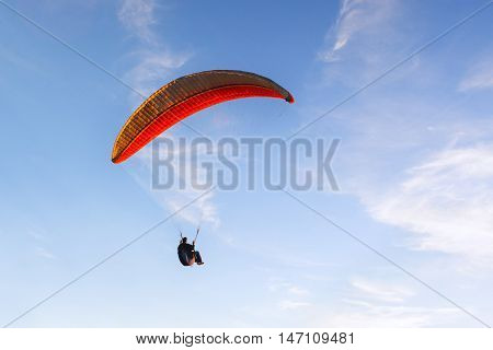 man flying on a paraglider against the evening blue sky
