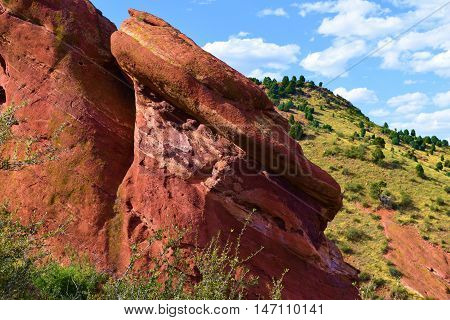 Red Rocks surrounded by rural hills and mesas taken at the Front Range of the Rocky Mountains in Red Rocks Park, CO