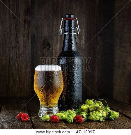 Beer bottle with drops and lager beer glass with raspberries and hops on wooden table