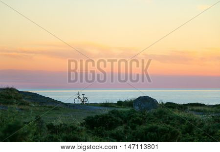 Silhouette of bycicle on the beach at sunset.