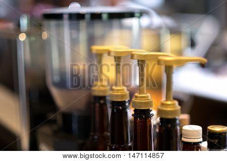 Sauce bottles in row with blur background. Kitchen equipment.