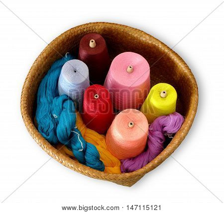 Spools of thread in a wicker basket in white background with top view
