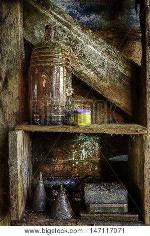 Shelf on old shed wall  with old bottle and old fashioned oil cans