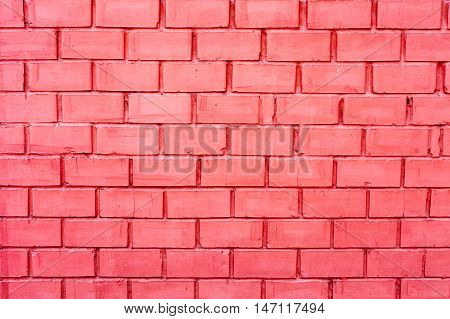Brick wall made of bricks painted in pink. The texture of a brick wall. The horizontal masonry. Texture as background with a copy of the space.