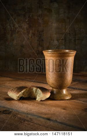 Communion wine cup and bread on wooden table