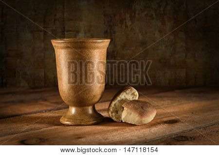 Wine goblet and bread as symbols of Communion on wooden table
