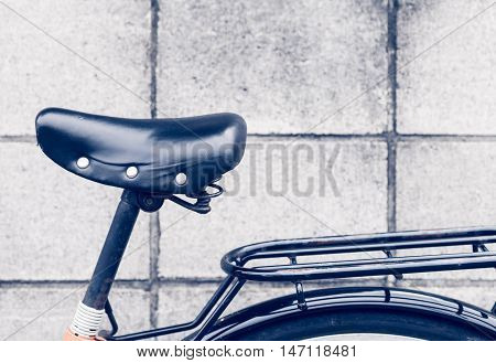 Close - up Black leather saddle and stacks bike