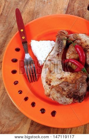 grilled chicken thighs on orange plate with white rice and red hot chili pepper knife and fork on light wooden table