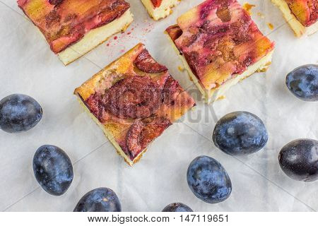 Top View on plum cake with cinnamon on baking paper with plums