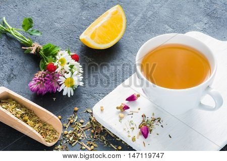 Cup of green tea, lemon wedge, rose buds and bouquet of flowers. Concept of antioxidant beverage, healthy lifestyle, dieting, well-being. Horizontal