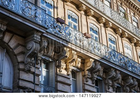 Ornate facade of a building with wrought iron balconies and shadows from opposite houses  in Toulouse, France