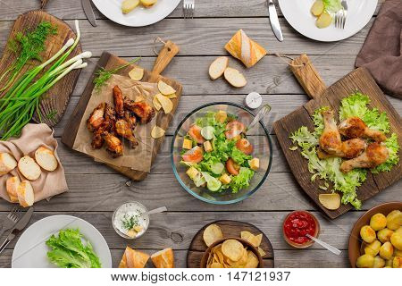 Outdoors Food Concept. On the wooden table different food grilled chicken legs buffalo wings bread salad potatoes potato chips and sauces