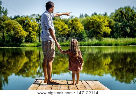 Dad with daughter on shoulders stand on the pier near the lake