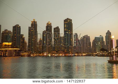 cityscape, travel, tourism and urban concept - Dubai business city district night lights and seafront