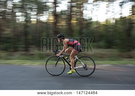 Energetic sportive girl rides a bike on the road on the nature background. She wears black-pink sportswear, a black helmet, sunglasses and green sneakers. Shoot from the side. Horizontal.