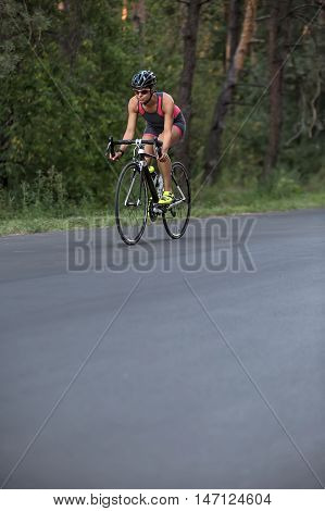 Attractive sportive girl rides a bike on the road on the nature background. She wears black-pink sportswear, a stopwatch, a black helmet, sunglasses and green sneakers. Vertical.
