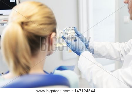 people, medicine, stomatology and health care concept - happy male dentist showing jaw and teeth layout to patient woman at dental clinic office