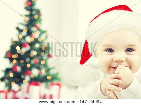 holidays, babyhood, childhood and people concept - happy baby in santa hat over christmas tree lights and gifts background