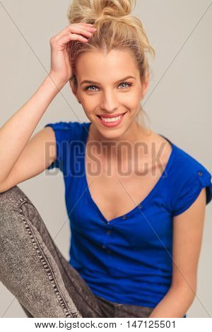 laughing young blonde woman sitting and holding her hand on forehead