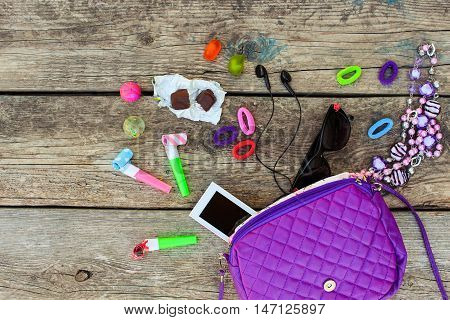 Children's handbag and accessories: mobile phone, whistle, hair bands, candy, beads, headphones, sunglasses, ball on old wooden background. Top view.
