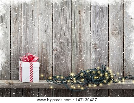 Christmas lights and gift box in front of wooden wall with snow. View with copy space for your text