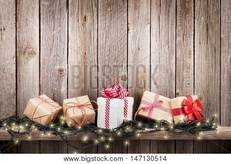 Christmas lights and gift boxes in front of wooden wall. View with copy space for your text