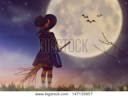 Happy Halloween! Cute little witch with a broomstick. Beautiful young child girl in witch costume outdoors.