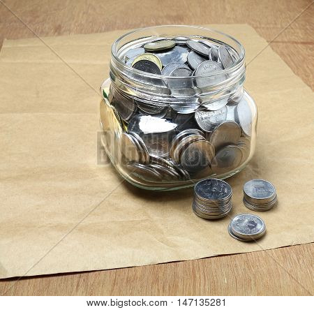Indian currency rupee coins in a bottle, and stacks of coins, indicating savings for investment, on a brown paper background.