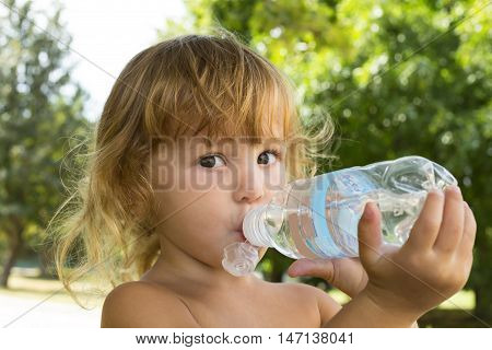 The Little Girl With Curly Golden Hair Pleasure Drinks Water From A Bottle.