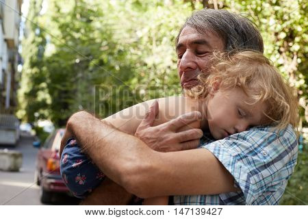 Little Girl And Father. Child Rests In The Hands Of His Father.