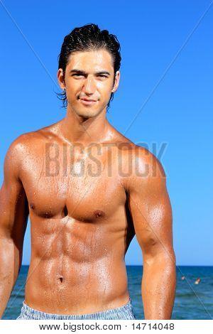 sexy caucasian fit man posing in a beach