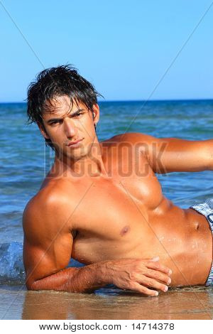 sexy caucasian fit man posing in a beach in Greece
