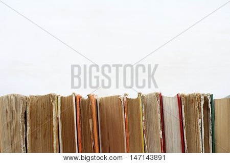 many old shabby books standing in a row on a light surface / used book shelf