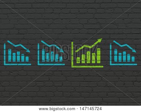 Finance concept: row of Painted blue decline graph icons around green growth graph icon on Black Brick wall background