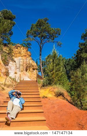 Middle-aged woman on the steps of photographing the park. Unique red and orange hills in the province of Languedoc - Roussillon, France