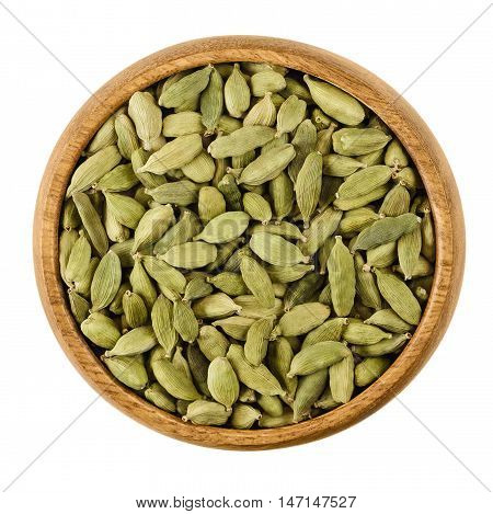 Cardamom pods in a wooden bowl on white background. Light green processed pods of Elettaria cardamomum, dried seeds, used as flavorings, spice and as medicine. Isolated macro photo close up from above
