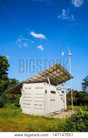 Solar power and wind turbine generator. Solar panels. Solar station against blue sky background. Renewable energy sources. Green energy concept. Outdoor at daytime on summer day.