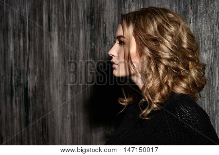 Profile portrait of blonde teenage girl standing by a grunge wall. Generation. Youth style, fashion.