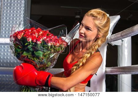 Boxing girl wearing boxing red gloves with presented bouquet flowers sitting in corner of boxing ring.