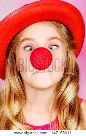 Funny little girl wearing clown nose and hat. Celebration, life events. Happy birthday.