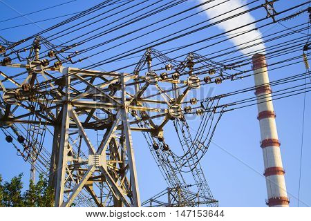 Big power lines and power station chimney in the sunny day with blue sky