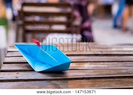 Origami blue paper ship lying on a table
