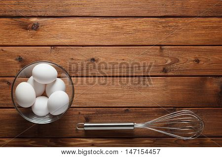 Eggs And Wire Whisk On Rustic Table