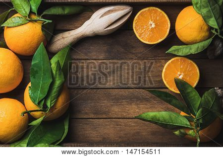 Fresh oranges with leaves in dark wooden tray over wooden background, top view, copy space, horizontal composition
