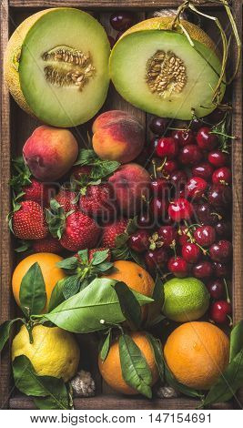 Healthy summer fruit variety. Melon, sweet cherries, peach, strawberry, orange and lemon on wooden tray background, top view,