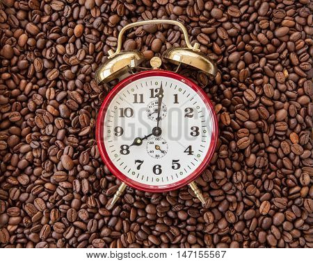 Vintage alarm clock showing 8 o'clock on a background of coffee beans