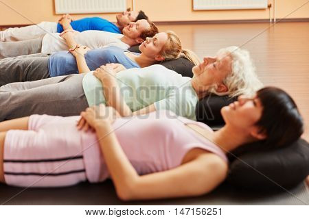 Senior and group during breathing exercise for relaxation at yoga class