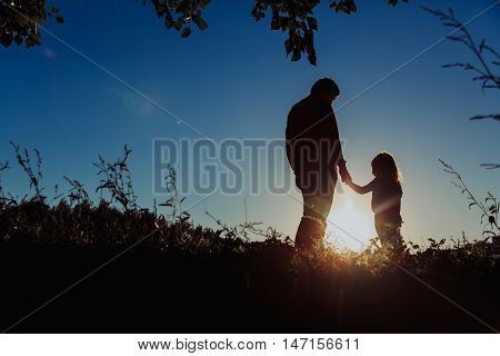 father and little daughter holding hands at sunset sky