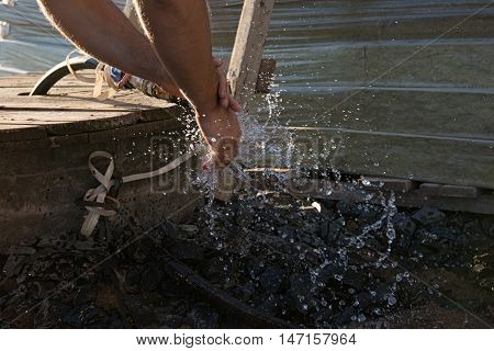 A pair of male hands are being washed in stream of water